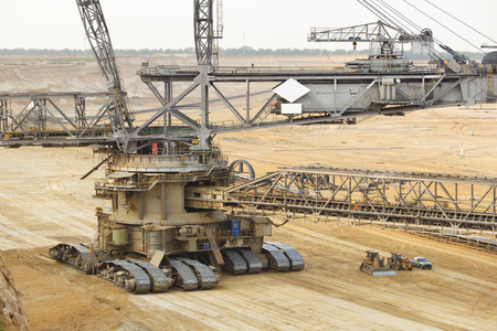 A lignite surface mine with a giant bucket-wheel excavator, one of the worlds largest moving land vehicles. The little cars and construction vehicles show the scale.