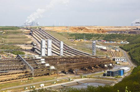 A brown coal pit mine with conveyor belts leading to a distant coal power station.