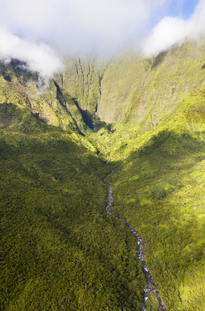 View from helicopter into the Blue Hole in the center of Kauai, Hawaii. The canyon walls of the Waialeale in the background are roughly 1000m high. Since it is one of the rainiest spots on earth it is quite rare to see it with blue sky.