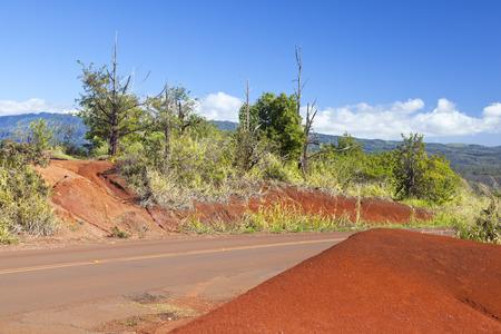 A road crossing an area of intensely red soil near Waimea Canyon in Kauai, Hawaii. Stock Photo