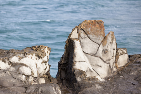 Cooled volcanic rock by the sea in the shape of teeth in the northwest of Maui, Hawaii. The place is called Dragons Teeth. Stock Photo