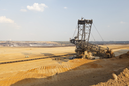 A lignite surface mine with a giant bucket-wheel excavator, one of the worlds largest moving land vehicles. See the tiny looking construction vehicles and cars next to it.