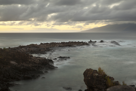 Reefs at Napili Point at dusk in Maui, Hawaii with Molokai in the background.