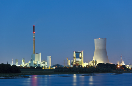 Old and new coal power stations side by side with reflection in the water and night blue sky. The new cooling tower has a height of 180m which makes it one of the highest in the world. 写真素材