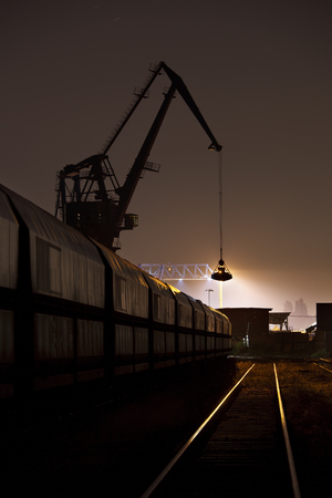 Night view of railroad tracks, a train and a tall crane in a coal harbor.
