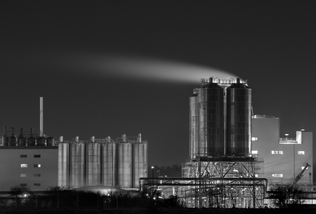 Detail view of a chemical plant in black and white with shiny storage tanks.