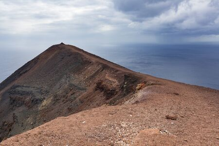 Peak of the colorful crater of the volcano Teneguia in the south of La Palma above the sea.