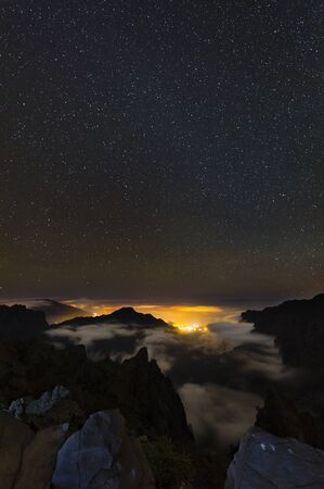 Starscape above the Caldera de Taburiente in La Palma, Spain with illuminated villages below the clouds. Stok Fotoğraf