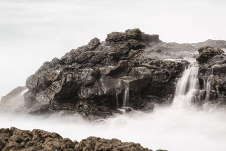 Long exposure of volcanic lava rocks in the south of La Palma, Spain with waterfalls from the surf.