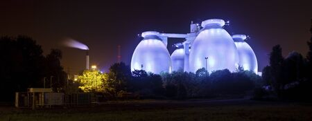 A sewage plant with blue illumination at night, looking surreal like an extraterrestial space ship.