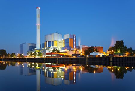 A colorful industrial building at a canal with clean reflection and night blue sky.
