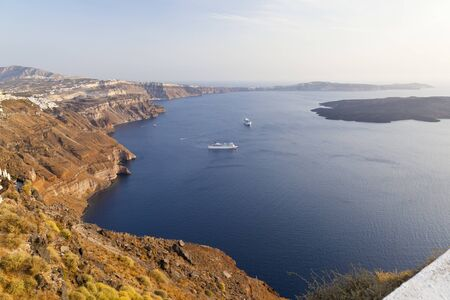 View from Imerovigli over the Santorini caldera with Nea Kameni to the right in warm evening light.