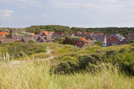 A little village in between overgrown sand dunes in Norderney, Germany. Banco de Imagens - 132126493