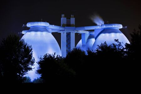 Futuristic digestion towers of a sewage treatment plant illuminated in blue.