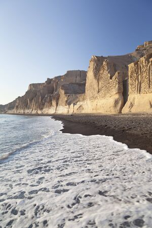 The long Vlychada Beach of Santorini with its impressive pumice cliffs in evening light.