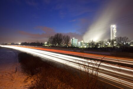 Light trails on a highway in front of a chemical plant with night blue sky. 写真素材