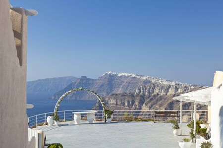 View of a wedding setup in the south of Santorini to the center with the villages on the crater rim.