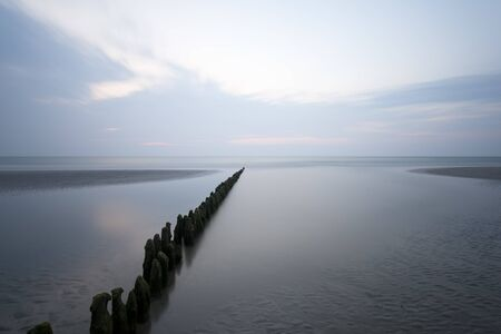 A row of poles leading into the North Sea in Norderney, Germany. Long exposure shot. 写真素材
