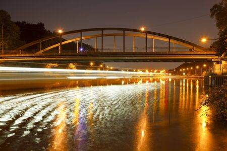 Night shot with a ships light trail and reflection in front of a bridge short before a canal lock.