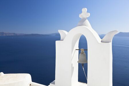 White bell tower of a little chapel in Oia, Santorini with the caldera as background.