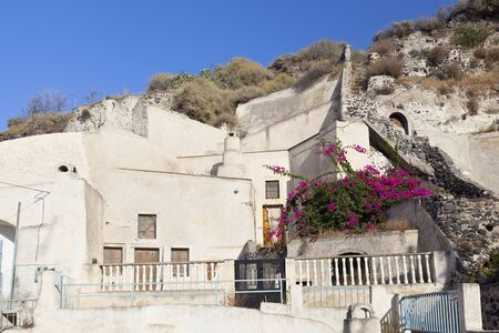 Houses built with caves into the pumice stone hills in little village Vothonas with blue sky. Santorini, Greece.