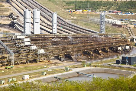 A lignite coal surface mine with conveyor belts leading to a distant coal power station.