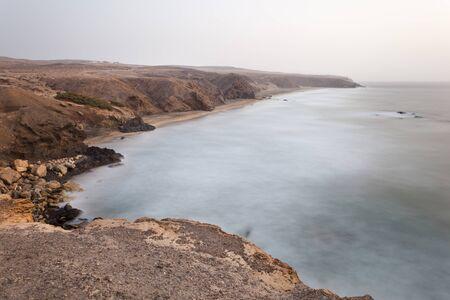 Beach and rocky coastline at La Pared, Fuerteventura during a slight sandstorm. Long exposure evening shot.