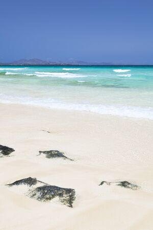 Beach and turquoise sea at Corralejo, Fuerteventura. The islands in the background are Los Lobos and Lanzarote.