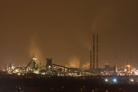 A dark and dirty looking steel and coking plant in the distance at night. Stok Fotoğraf