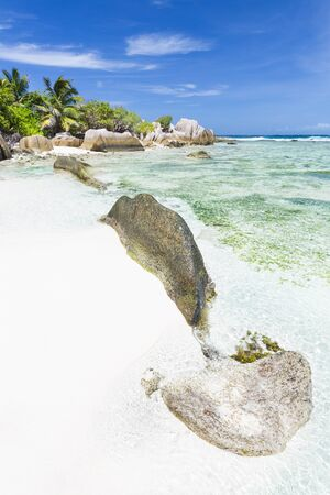 The beautiful tropical beach Anse Source D'Argent in La Digue, Seychelles with clear water, granite rocks and palm trees