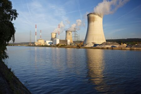Daytime shot of a nuclear power plant at a river with blue sky and some clouds as well as clean reflection.