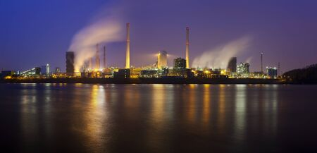 Panorama of a coking plant seen over a river with a lot of steam and night blue sky. Zdjęcie Seryjne