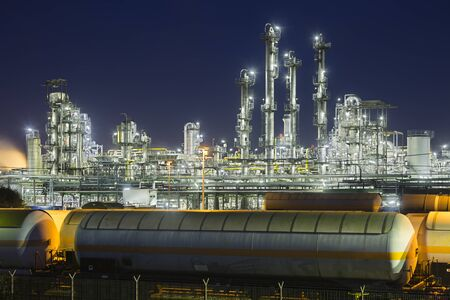 Industrial trains in front of refinery distillation towers with night blue sky.