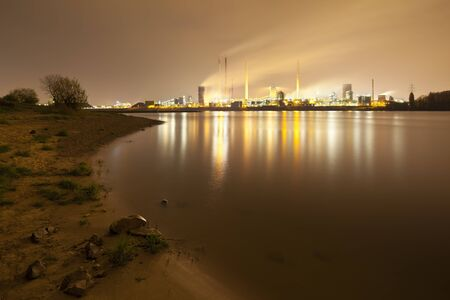 A coking plant seen over a river with a lot of steam, the rivershore in the foreground. Zdjęcie Seryjne