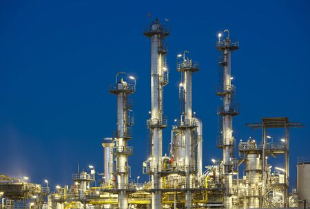 Illuminated distillation towers of a refinery with perfect night blue sky.