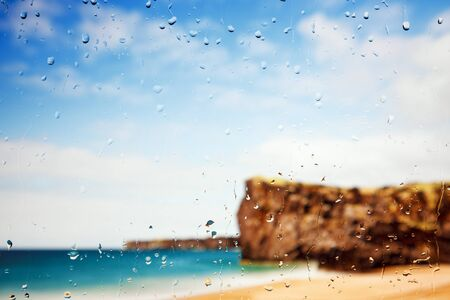 A golden beach and cliffs seen through a raindrop covered window.