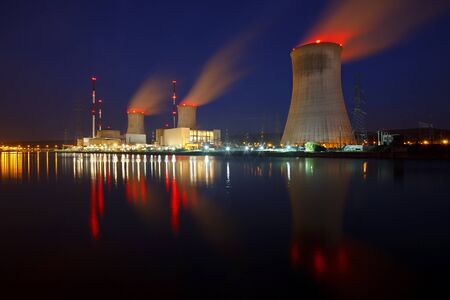Night shot of a large nuclear power plant close to a river with blue night sky. Zdjęcie Seryjne