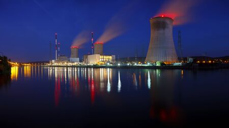 Panoramic night shot of a large nuclear power plant close to a river with blue night sky. Tihange, Belgium. Zdjęcie Seryjne