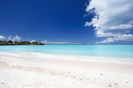 A clean white caribbean beach with deep blue sky and turquoise water.