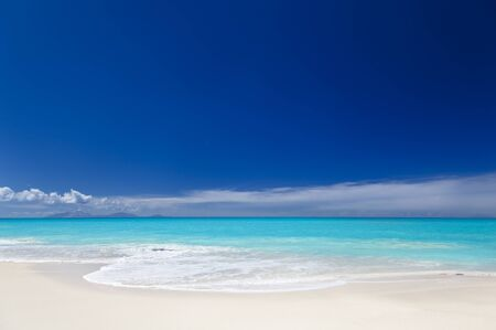 A clean white caribbean beach with deep blue sky and turquoise water. The island of Montserrat on the horizon. Stock Photo