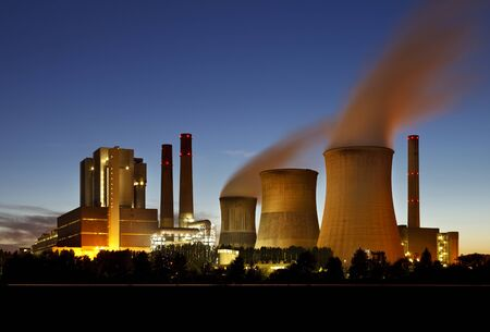 Brown coal power station with night blue sky and steam.