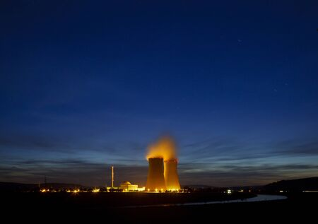 Night shot of a nuclear power plant close to a river with blue night sky.