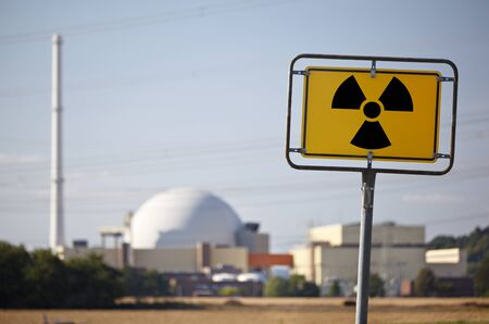 A radioactive warning sign in front of a nuclear power plant.