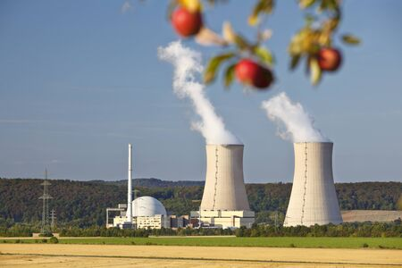 Some red apples hanging 'above' the cooling towers of a nuclear power plant.