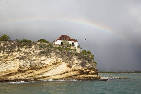 The ruins of Fort James in Antigua seen from a boat with a slight rainbow.