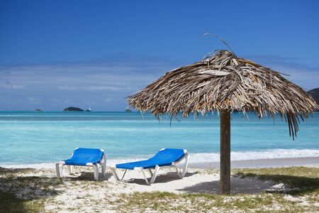 Two beach chairs and a fixed umbrella on a caribbean beach.