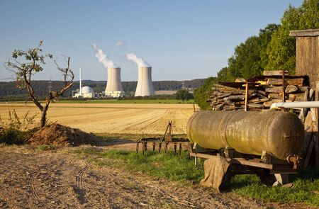 An apple tree and old agricultural machines in the foreground of a nuclear power plant, contrast between nature and environmental damage.