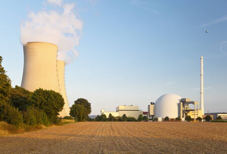 Reactor building, smoke stack and two cooling towers of a nuclear power station, an empty field in the foreground.