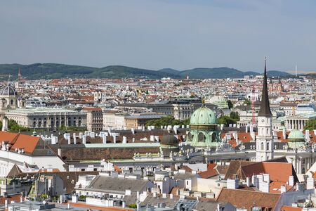 View to the Hofburg of Vienna, Austria with blue sky and some hills in the background.