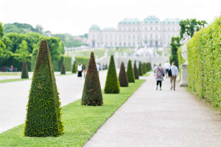 View along paths in the Belvedere Palace park of Vienna, Austria with blurred tourists in the background.